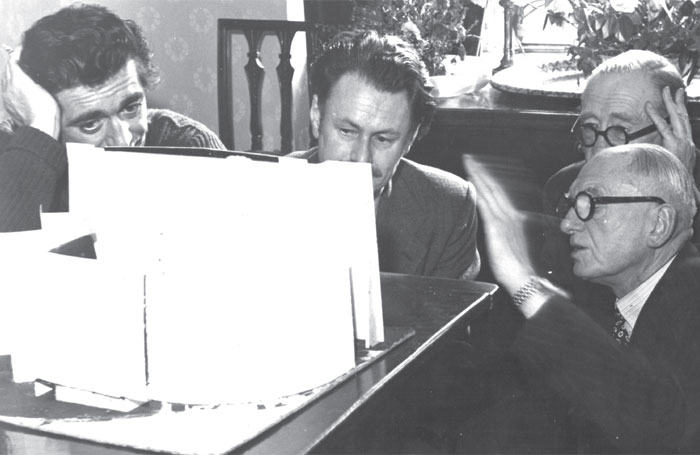 Producer, director and actor Terence de Marney, designer Guy Sheppard, scenic artist Phil Harker and Ted Loveday Snr discussing a set for the 1953 Garrick Theatre production of Dangerous Curves