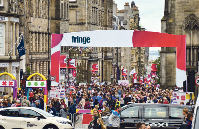 Festivalgoers throng the Royal Mile at the Edinburgh Festival Fringe. Photo: Lou Armor/Shutterstock