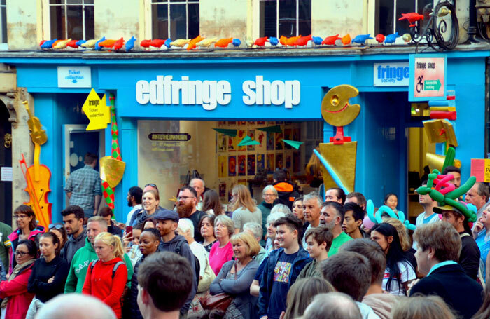 Crowds watching a street show outside the Edinburgh Fringe box office on the Royal Mile in 2018. Photo: Lou Armor/Shutterstock