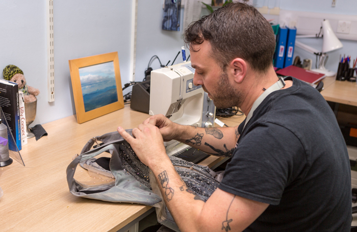 Ben Edmonds from the National Theatre repairing one of the costumes from Mirror Mirror. Photo: Lucy Barriball