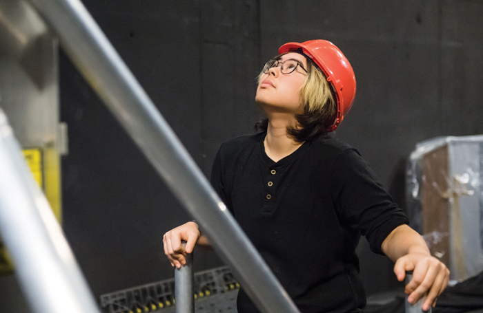 A theatre technician stabilises a ladder while observing changes to the lighting rig. Photo: Alex Brenner