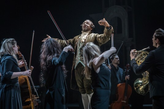 A scene from Amadeus, centre  Lucian Msamati as Antonio Salieri with members of Southbank Sinfonia. Image by Marc Brenner